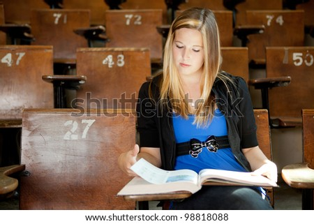 Young college girl looking at text book in lecture hall