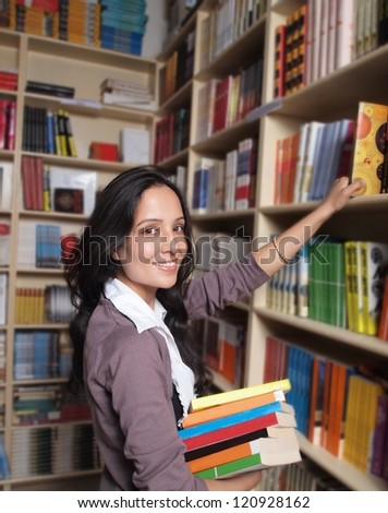 Young College student holding books in the campus library.