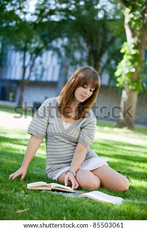 Young college student reading book on campus lawn