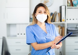 Young  colombian female medical mask in uniform holding clipboard in doctor's office