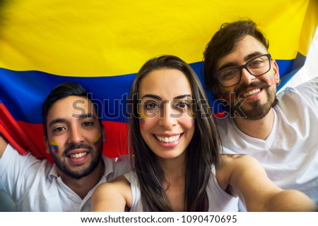 Young colombian soccer fans taking a selfie with a flag in their backs - Shutterstock ID 1090470695