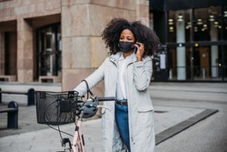 Young commuter woman in city in sustainable home-to-work path wearing face mask against Coronavirus Covid-19 pandemic walks with bike while on business call from smartphone - Safety commuting concept