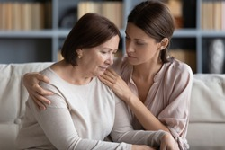 Young compassionate woman embracing shoulder of unhappy stressed middle aged mommy, comforting her at home. Kind grownup daughter supporting caring of older mature mother, sitting together on couch.
