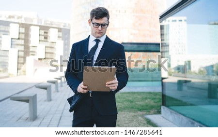 Young concentrated businessman in trendy suit and eyeglasses holding clipboard and reading document standing on background of modern city street