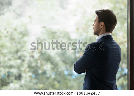 Young concentrated caucasian businessman ceo manager or executive standing near large office window planning new project or goal, looking forward company development, making decision. Copy space Сток-фото ©