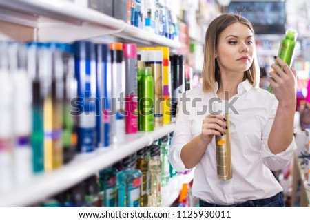 Young concentrated woman looking for haircare cosmetics in a shop