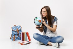 Young concentrated woman student holding world globe searching learning about countries sitting near backpack, school books isolated on white background. Education in high school university college