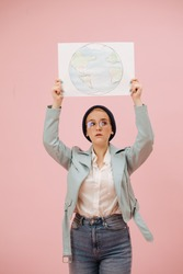 Young concerned female eco activist in a cap and round glasses holding planet earth banner above her head. Over pink background. She has short hair, wearing mom jeans and turquoise leather jacket.