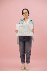 Young concerned female eco activist in a cap and round glasses showing planet earth banner. Over pink background. She has short hair, wearing mom jeans and turquoise leather jacket.
