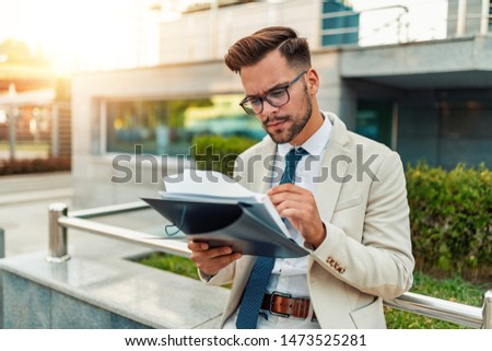 Young confidant businessman holding documents in hands outdoors. #1473525281