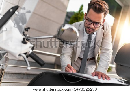Young confidant businessman holding documents in hands outdoors. #1473525293