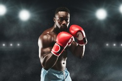 Young confident african american boxer standing in pose and ready to fight, stadium background, copy space