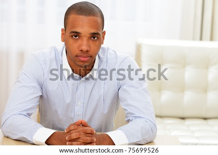 Young confident african american businessman sitting at the table