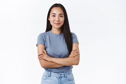 Young confident and determined asian girl start her first day work, assertive everything go well, cross hands chest in self-assured pose, smiling pleased, stand white background