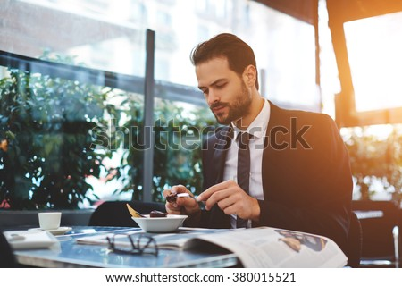 Young confident businessman in luxury suit having breakfast in modern coffee shop during work break, serious male restaurant owner eating tasty dish which was prepared chief cook specially for him