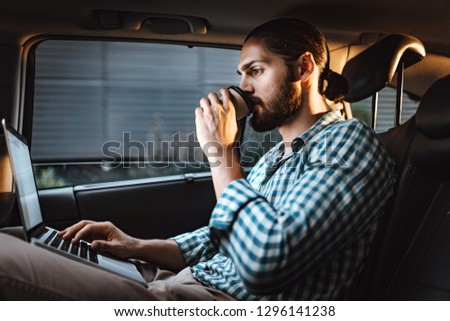 Young confident businessman is holding a cup of coffee in his hand, drinking and texting on a laptop on the back seat in car.