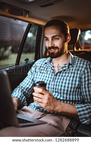 Young confident businessman is holding a cup of coffee in his hand, drinking and texting on the back seat in car.