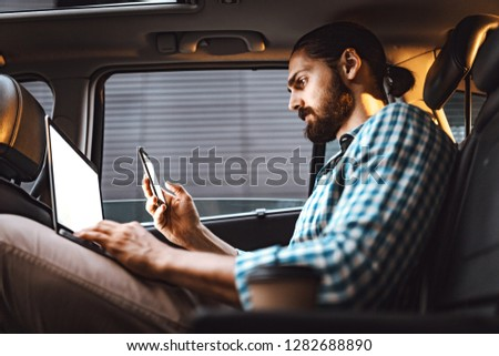 Young confident businessman is holding laptop and smartphone in his hand and texting on the back seat in car.