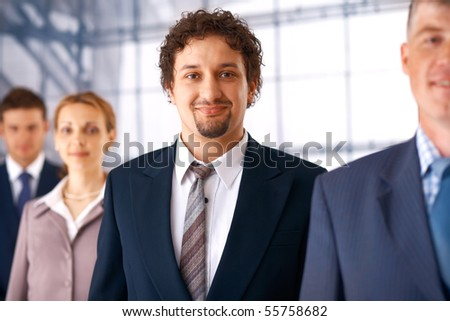 Young confident businessman standing in the row with his colleagues. - stock photo