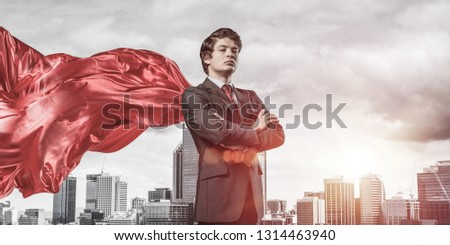 Young confident businessman wearing red cape against modern city background #1314463940