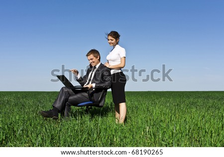 Young, confident businessmen working on laptop. Green lawn, spring