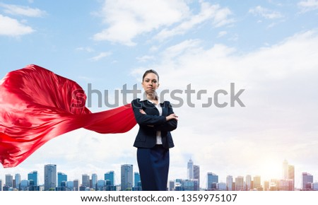 Young confident businesswoman wearing red cape against modern city background #1359975107