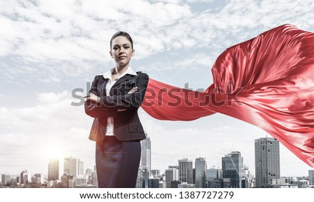 Young confident businesswoman wearing red cape against modern city background #1387727279