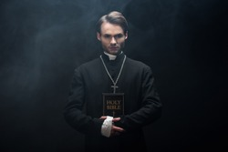young confident catholic priest looking at camera while holding holy bible on black background with smoke