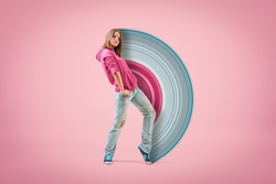Young confident girl in pink hoodie and light blue ripped jeans standing with hand on hip looking at camera on light pink background with paintbrush visual effect. Teen fashion. Street style.
