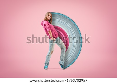 Photo of  Young confident girl in pink hoodie and light blue ripped jeans standing with hand on hip looking at camera on light pink background with paintbrush visual effect. Teen fashion. Street style.