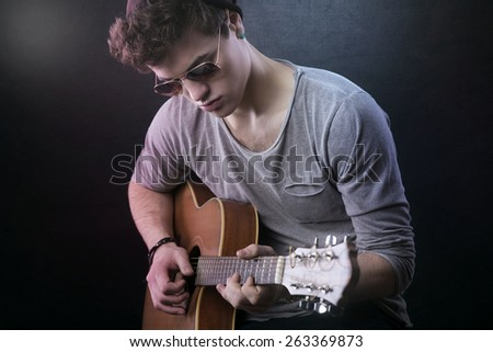Young confident guitarist playing his acoustic guitar on dark background