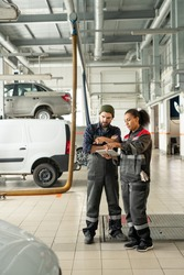 Young confident technicians in workwear pointing at one of cars in workshop while discussing its technical characteristics before repairing it