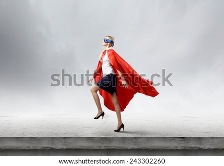 Young confident woman in super hero costume - Shutterstock ID 243302260