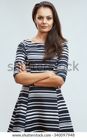 Young confident woman standing against gray background with crossed arms. Female model with long hair.