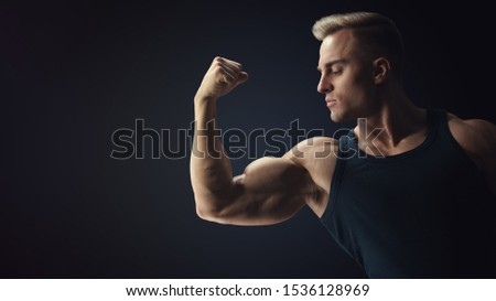Young confindent muscular bodybuilder guy standing on black background and posing biceps muscle Classic bodybuilding