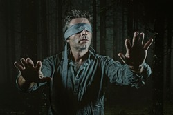 young confused and scared man blindfolded with necktie playing internet trend dangerous viral challenge with eyes blind lost in dark forest background guided by intuition