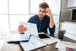 Young confused man analyzing finances at home while holding head with hand and looking at documents. Sitting near table with tablet.