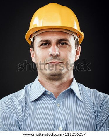 Young construction worker in hard hat on gray background - stock photo