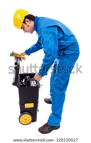 Young construction worker looking through his toolbox against white background