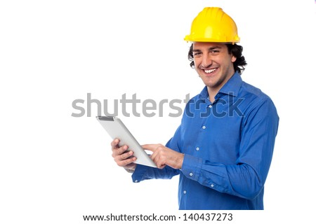 Young construction worker operating touch pad device.