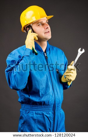 Young construction worker speaking on phone and holding a wrench against gray
