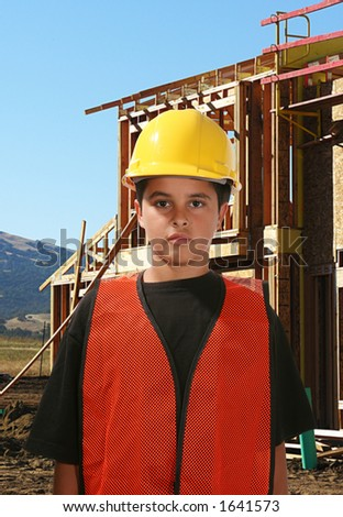 Young construction worker with house in progress in the background