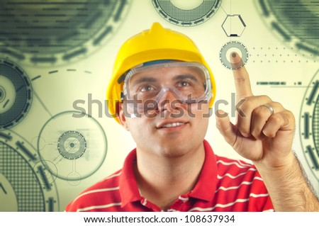 Young construction worker with yellow hard hat pressing a touch screen, focus on his index finger. Computer generated graphics as modern computer graphic interface for construction industry.