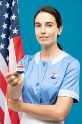 Young contemporary chambermaid in blue uniform showing you vote insignia while standing against stars-and-stripes background