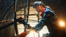 Young Contemporary Female Artist is Grinding Her Metal Tube Sculpture with a Handheld Power Tool in a Studio Workshop. Empowering Woman Makes Modern Brutal Abstract Artwork Out Of Metal.