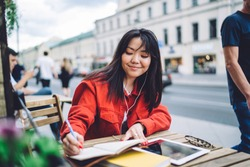 Young content Asian female student in causal jacket writing in notebook and listening to music through earphones while sitting at small table in modern outdoor cafe