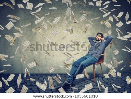 Young content man sitting on chair in rain of flying bills content with financial independence.