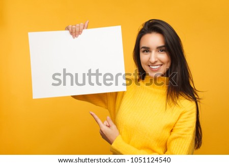 Young content model in yellow sweater holding and pointing at blank paper in hands smiling at camera.