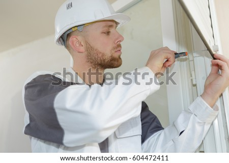 young contractor installing window blinds #604472411