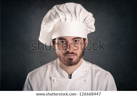 Young cook man wearing uniform close up portrait over grunge background.